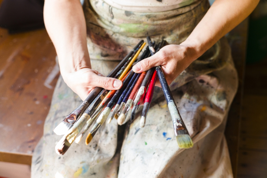 Close Up Of Woman Artist Painting Oils In His Studio, Holding Pe